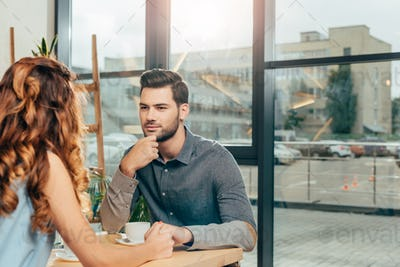 man looking at girlfriend while holding hands on date in coffee shop
