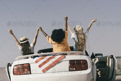 back view of friends holding hands while sitting in car with american flag at seaside