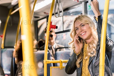 beautiful smiling blonde girl talking on smartphone while standing in public transport