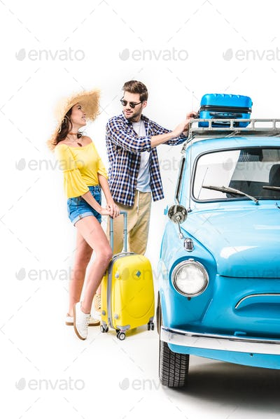 cheerful young couple of travelers putting luggage on car roof isolated on white
