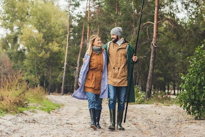 beautiful couple in raincoats with rods going from fishing