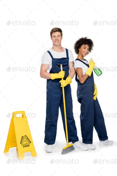 smiling multiethnic cleaners with cleaning supplies and warning sign looking at camera isolated on