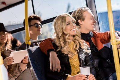 happy young couple embracing and laughing while sitting together in city bus