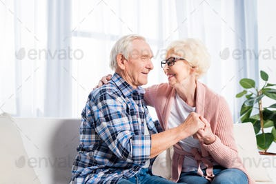 happy senior couple looking at each other and holding hands at home