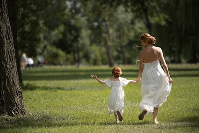 back view of beautiful mother and daughter in white dresses holding hands and walking in park