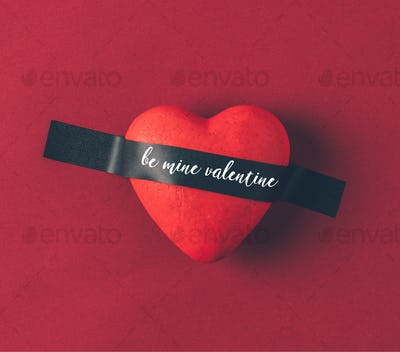Top view of red heart under insulating tape with words be mine valentine on red