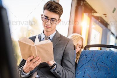 handsome young businessman in eyeglasses reading book in city bus
