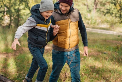 cheerful father and son holding hands while walking together in autumn forest