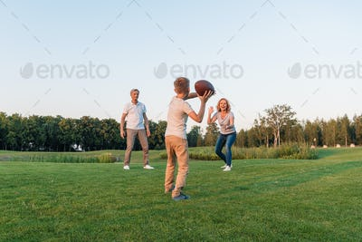 little boy going to throw rugby ball while playing american football with grandparents on green lawn