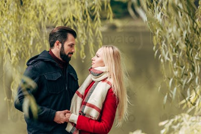 beautiful happy young couple holding hands and looking at each other in autumn park