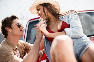 close-up view of young couple in love holding hands and smiling each other