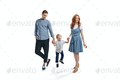 Happy family with one child holding hands and walking isolated on white