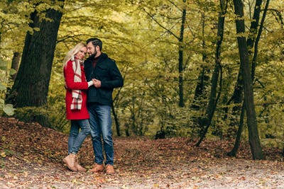 full length view of beautiful happy young couple holding hands and standing together in autumn park