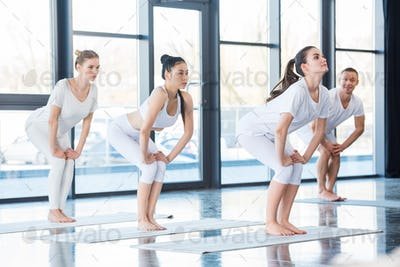 women doing chair pose (utkatasana) with instructor indoors