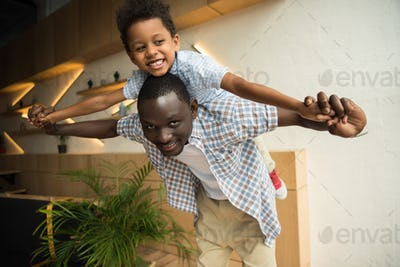 happy african american father piggybacking adorable little son indoors