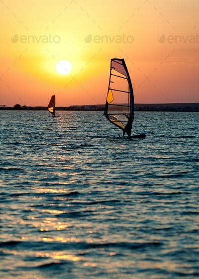 Still sea surface, man practicing wind surfing and golden sunset in sky