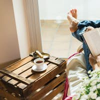 Young woman is relaxing at home, drinking tea, reading book