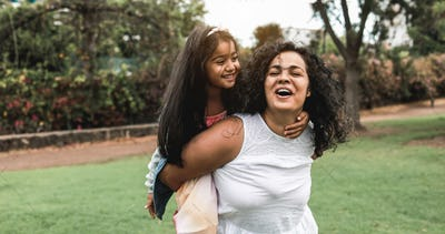 Happy indian mother having fun with her daughter outdoor - Soft focus on mom face