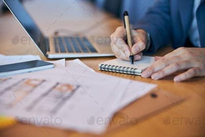 Female worker hands writing on spiral notebook