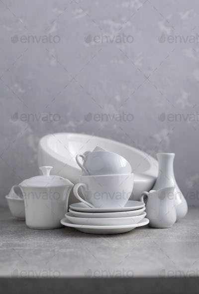 Empty crockery set or white ceramic dishes. White kitchen dishware and tableware on table