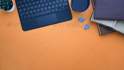 Stylish workplace with notebook ,coffee cup, keyboard and copy space on orange background.