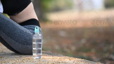 A bottle of water and sportswoman sitting and resting after workout at outdoor.