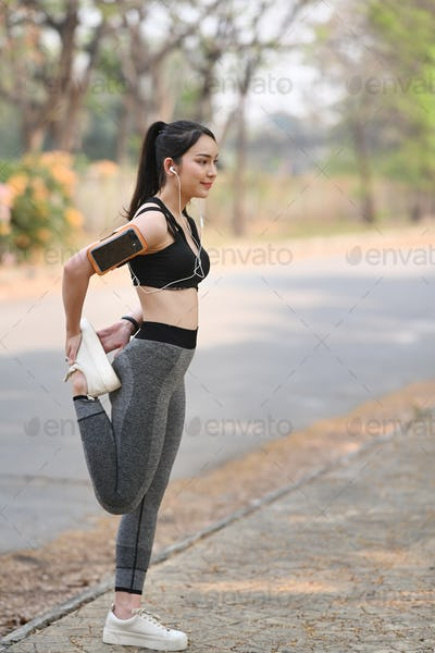 Portrait of young woman in sportswear stretching legs muscles before exercises outdoors.