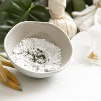 Spa composition with powder face mask and flowers.