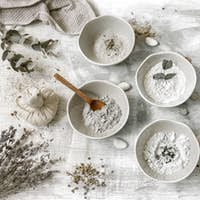 Spa composition with cosmetic clay powder on a textured background.