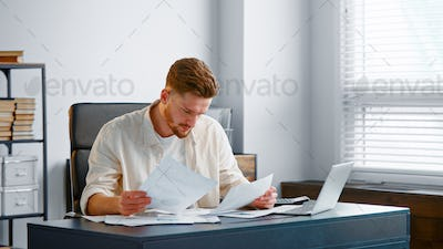 Corporate manager looks at sheets of papers with reports and analyzes company income