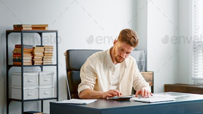 Professional accountant with beard counts paper checks summarizing sums on calculator