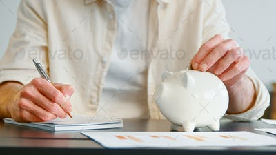Unrecognizable man pets white piggy bank and writes report in paper notebook