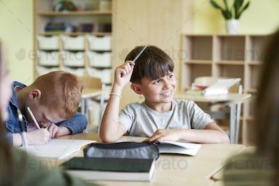 Happy boy thinking in classroom at school