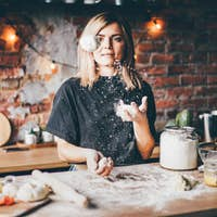 Woman having fun with flour in the kitchen.