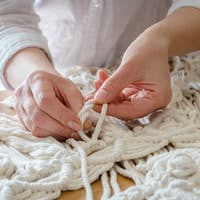 Macrame. Handmade macrame weaving and cotton threads on a rustic wooden stick. Scandinavian style in