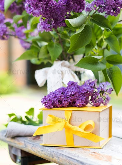 Gift box with yellow ribbon and lilac bouquets. A greeting card.