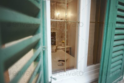 View through the half-open shutters and window on the interior of the bedroom
