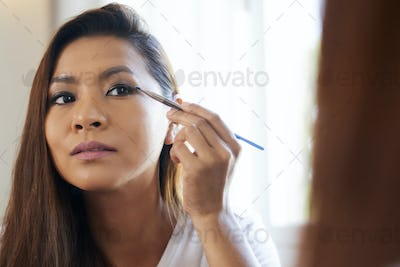 Concentrated Woman Applying Eye Shadows