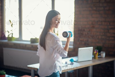 Delighted pretty woman exercising in the office