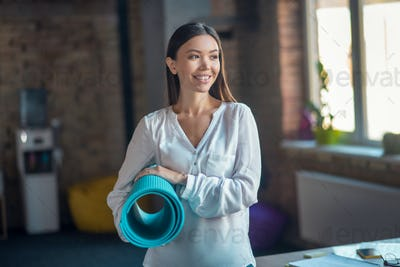 Joyful pretty woman standing with a yoga mat