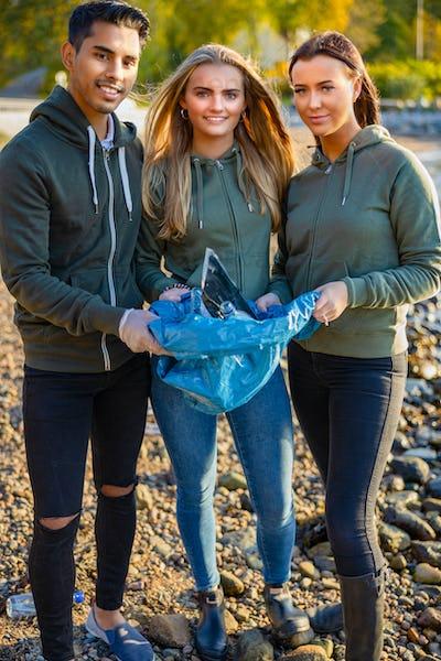 Smiling team of volunteers holding garbage bag at beach