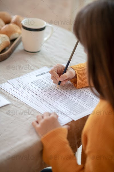Long-haired girl in orange outfit doing her homework