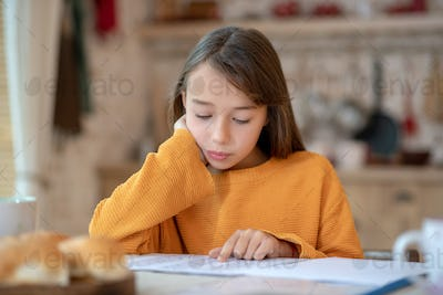 Cute girl in orange shirt looking concentrated