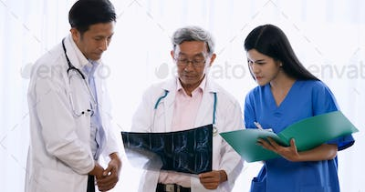 Doctor and medical assistants discussing about diagnosis result on x-ray film.
