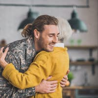 Young happy man in camouflage hugging his mom