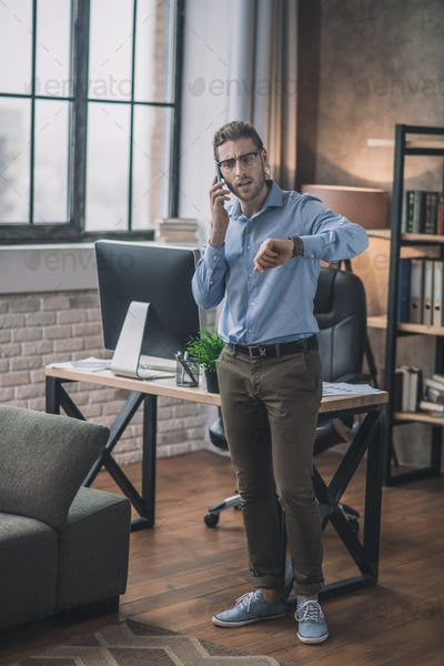 Young bearded businessman in blue shirt talking on the phone