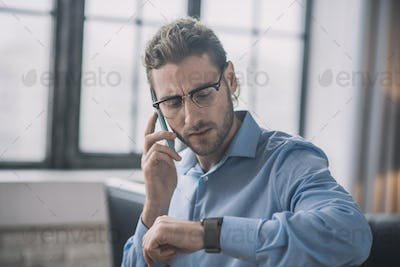 Young bearded businessman in blue shirt looking at his watch