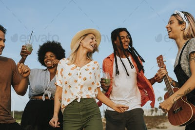 Friends singing and dancing at the beach