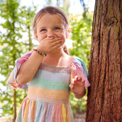 Smiling Young Girl Playing Hide And Seek Behind Tree In Garden