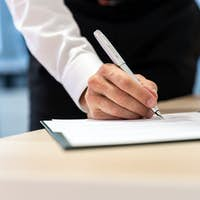 Businessman standing at his office desk signing a report